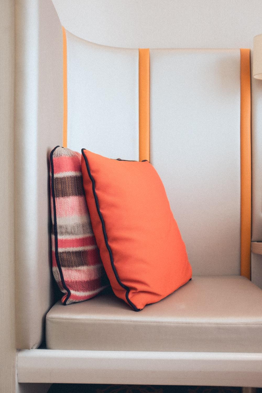 two standing orange throw pillows on sofa photo – Free ...