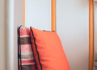 two standing orange throw pillows on sofa