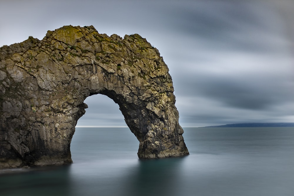 gray rock formation on body of water