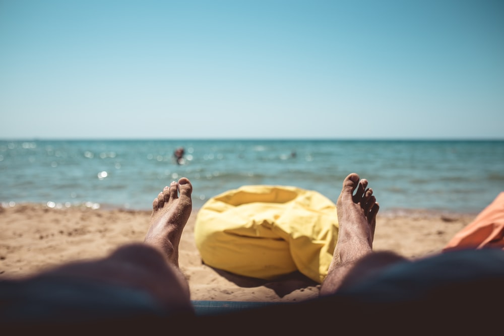 lying person on sand beside yellow bean bag during daytime