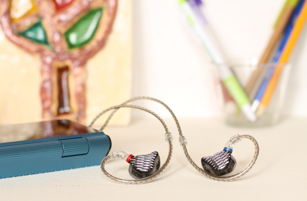 black-and-gray earbuds on selective focus photography