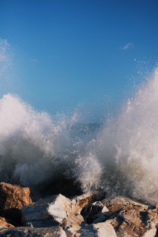 ocean waves crashing on rock formation