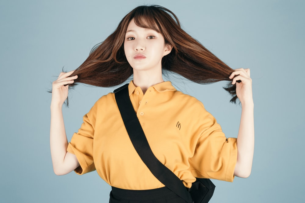 woman in orange polo shirt holding her hair
