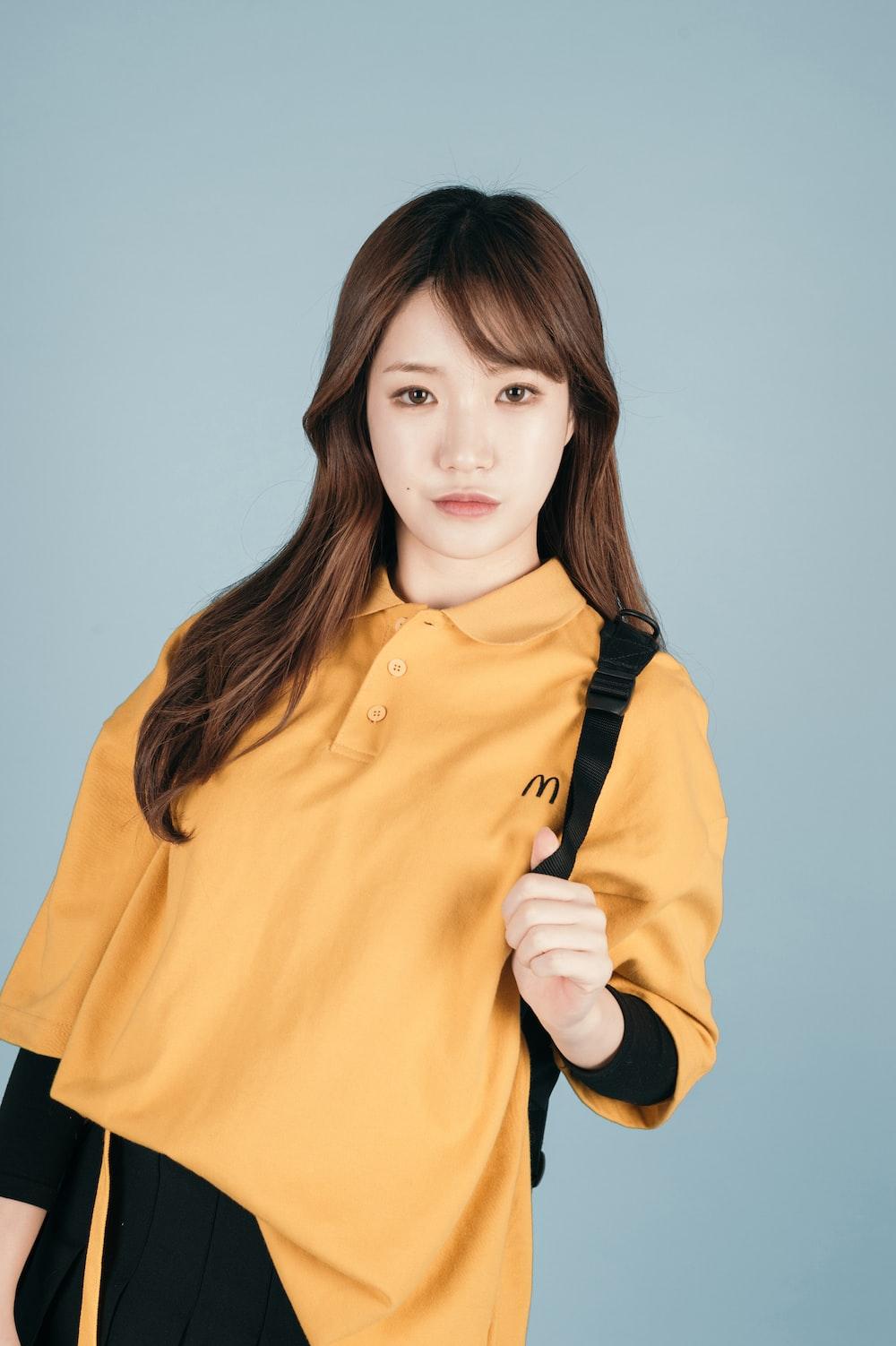 woman in yellow polo shirt taking pose
