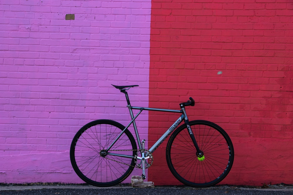 gray rigid bike leaning on wall during daytime