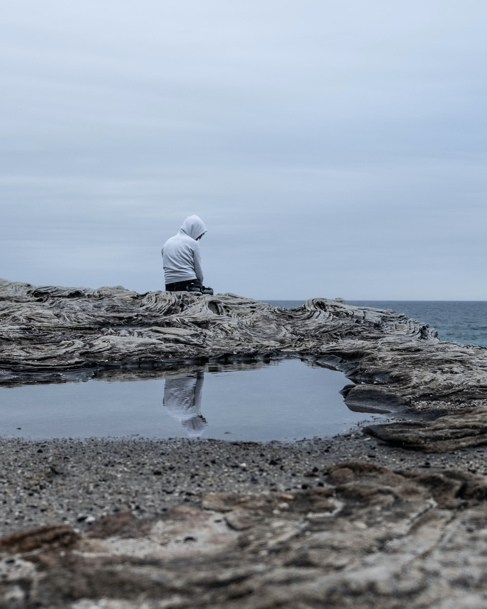 a man sitting on cliff overlooking a gloomy sea