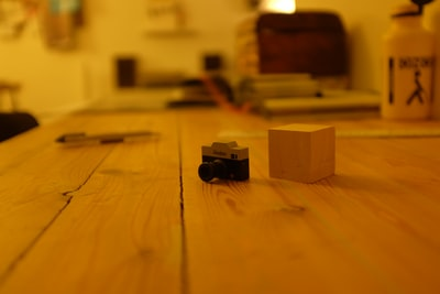black and gray camera and brown wooden cube