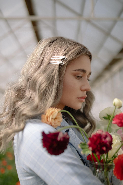 woman wearing grey shirt carrying flowers inside greenhouse