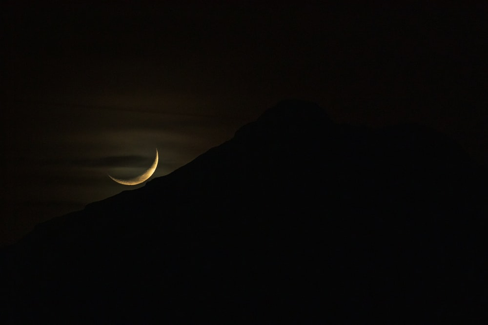 silhouette of mountain with crescent moon