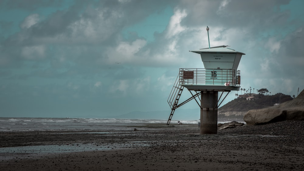 white and gray concrete lifeguard house under cloudy sky during daytime