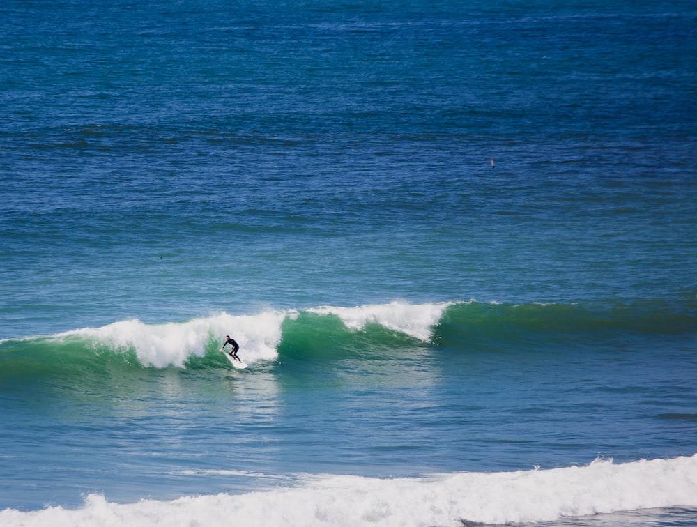 man doing stunt on surfboard during daytime
