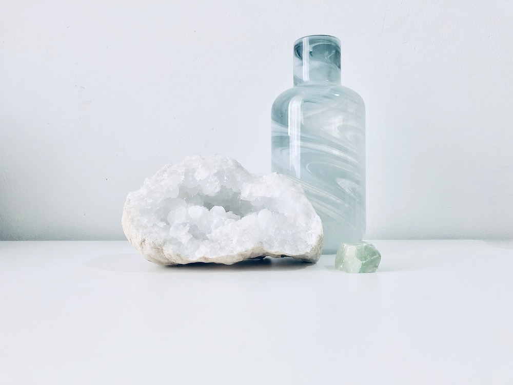 white geode beside clear bottle