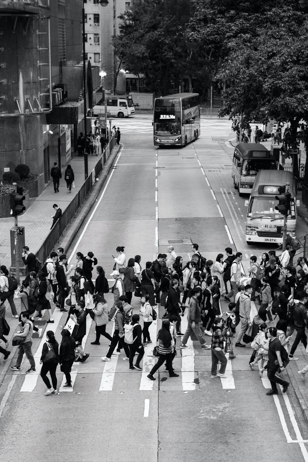 grayscale photography of people crossing road