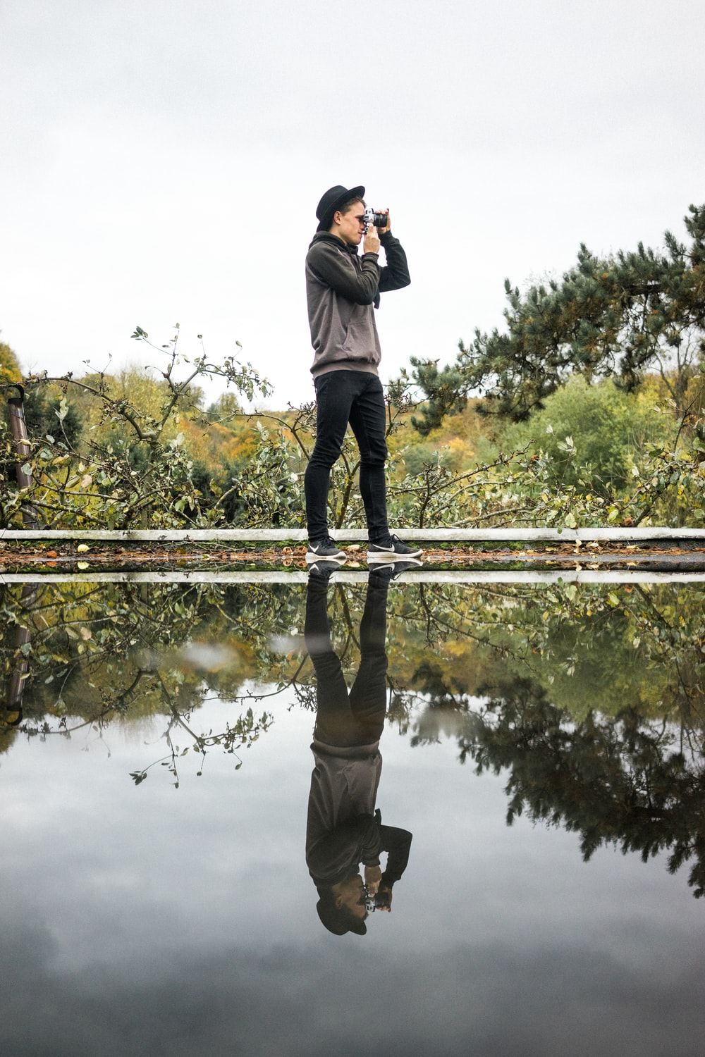 man standing near body of water using camera