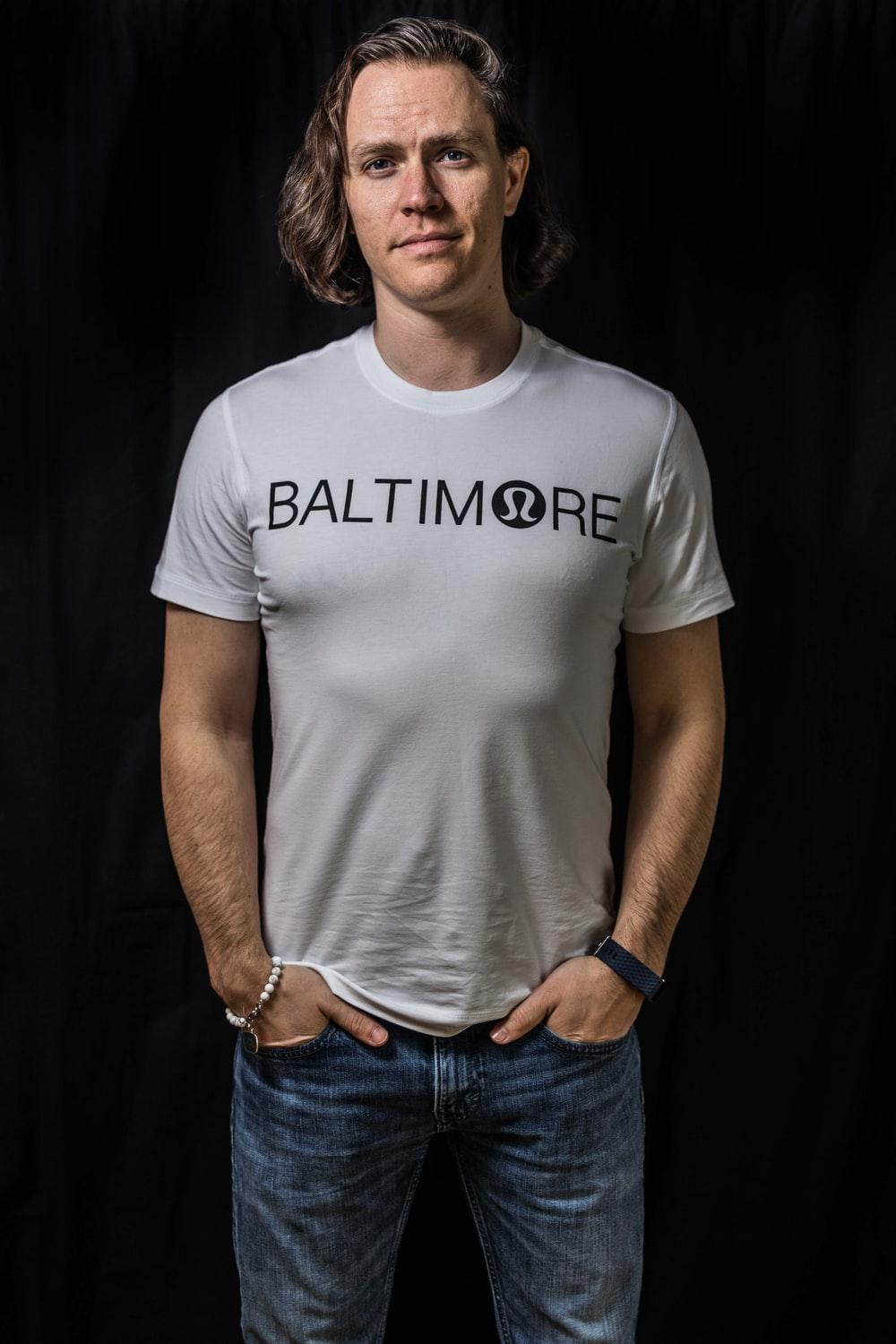 man in white Baltimore t-shirt and blue jeans