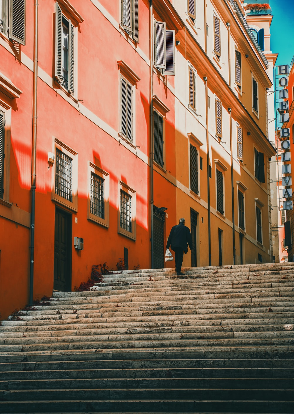 man walking on stairs beside building