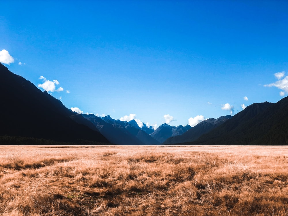 brown grass surrounded with mountains under blue sky