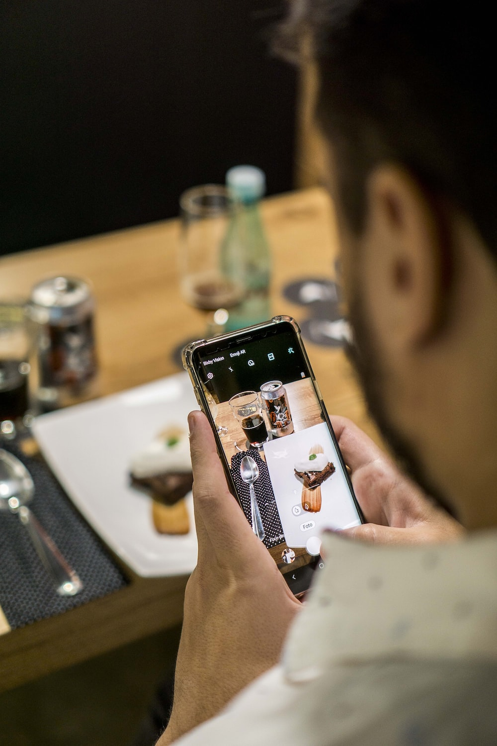 man taking photo using black Android smartphone