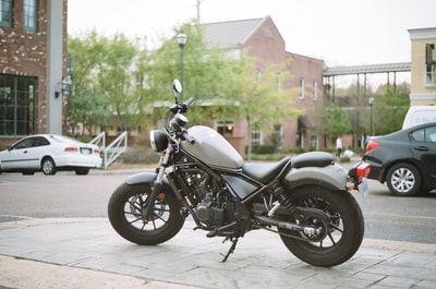white and black cruiser bike parked beside black sedan during daytime mississippi zoom background