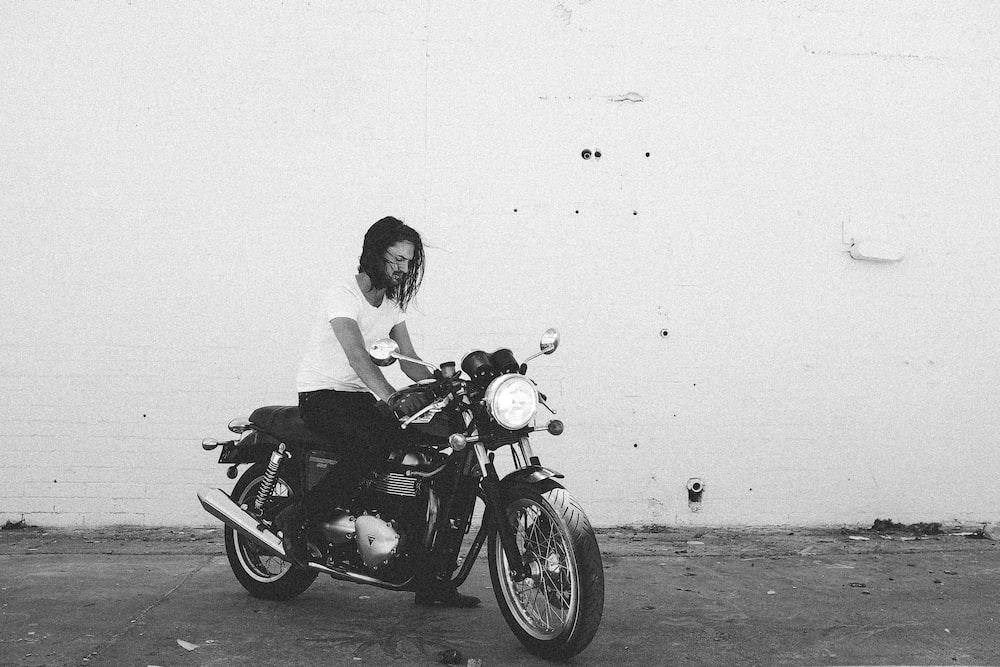 man riding motorcycle near wall