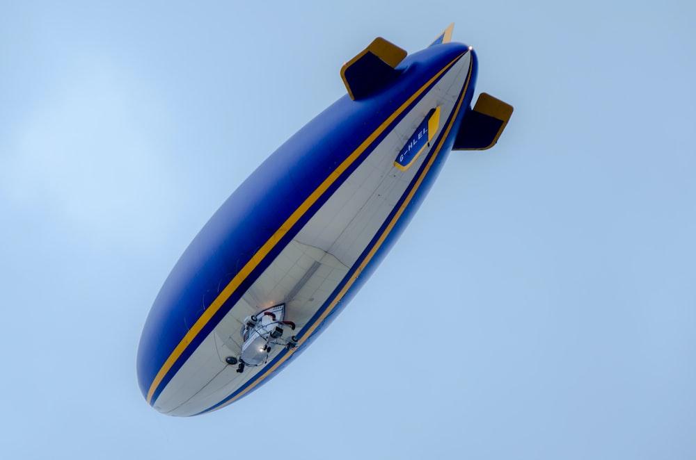 blue and white blimp flying under blue sky