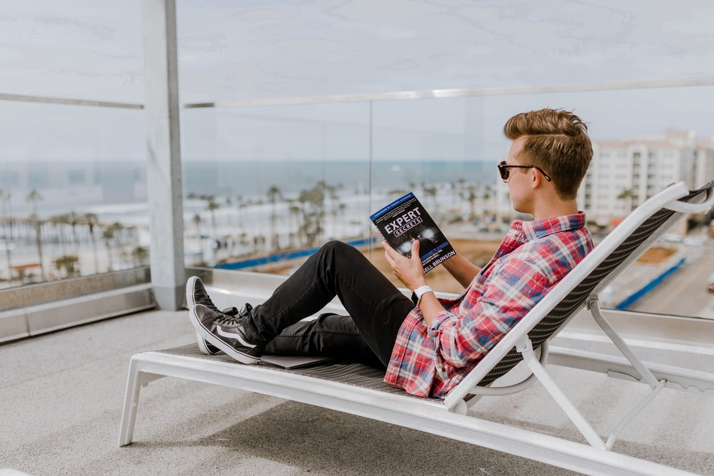 man sitting lounge chair reading a book