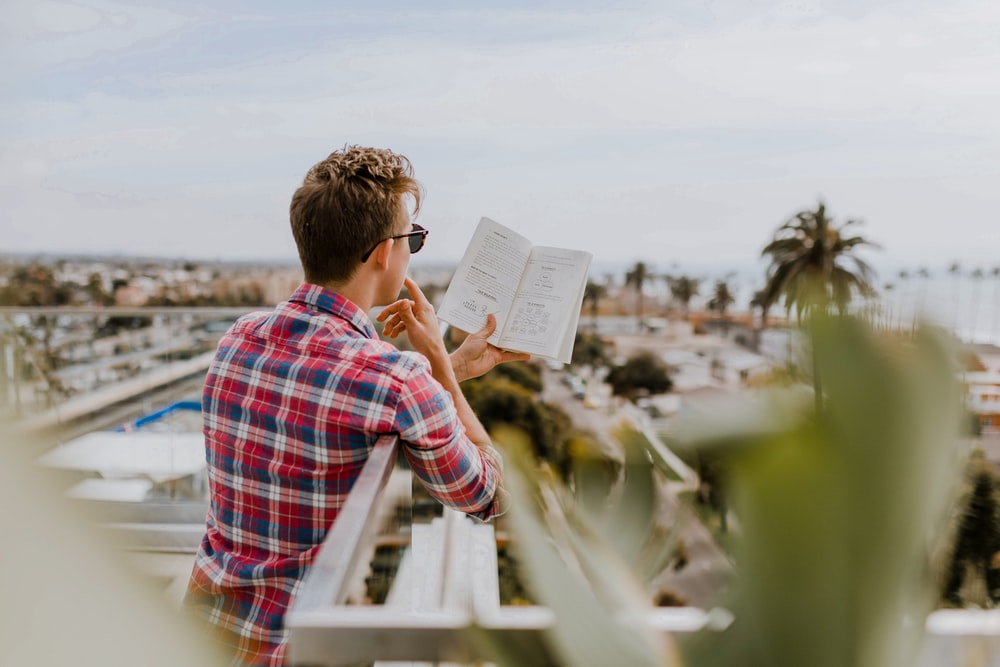 man reading book on balcony during daytim