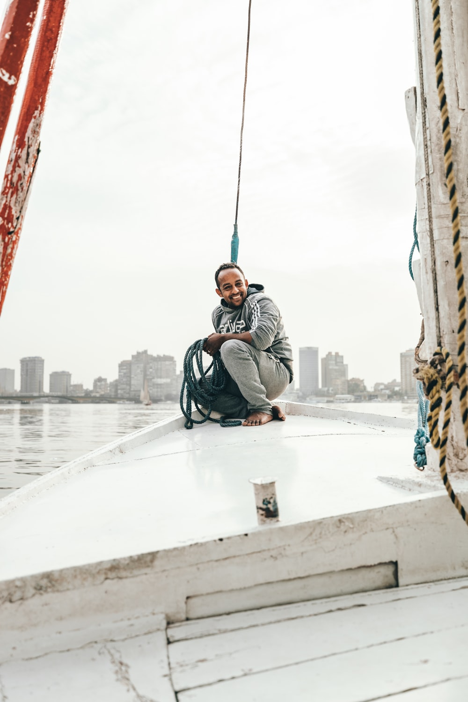 man sitting on boat during daytime