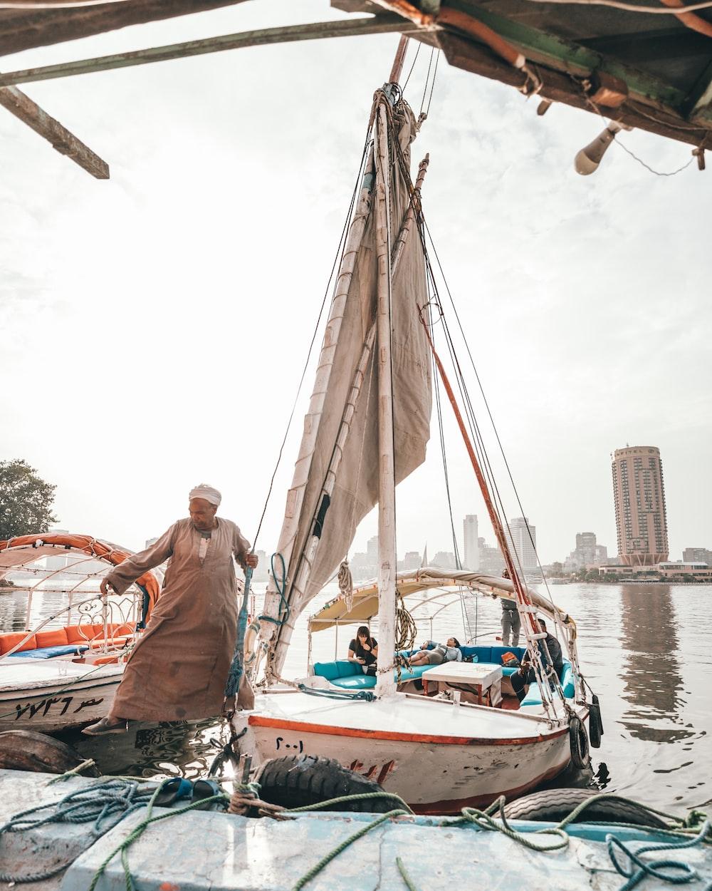 man standing near sailing boat