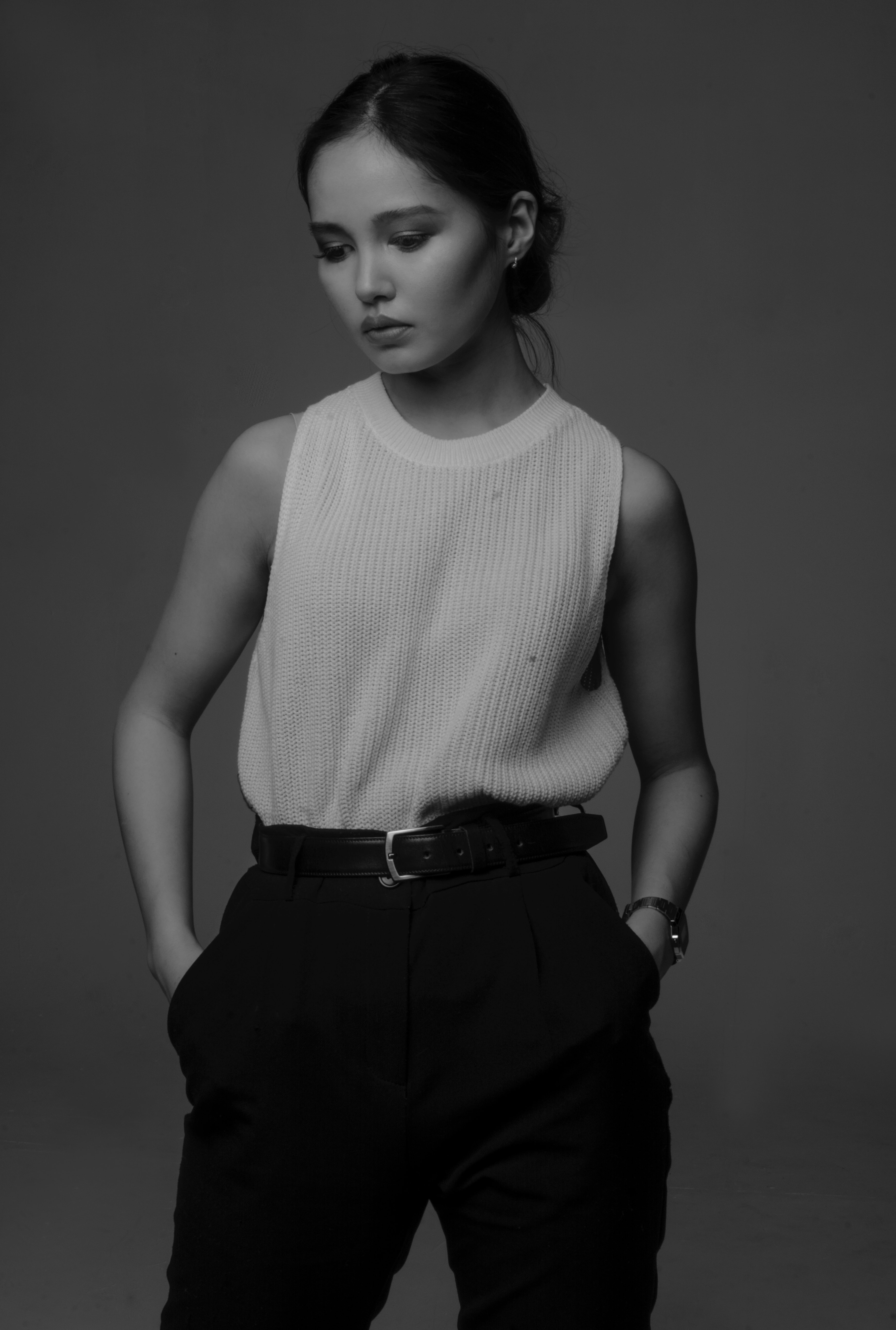 grayscale photo of woman in crew-neck sleeveless top and dress pants