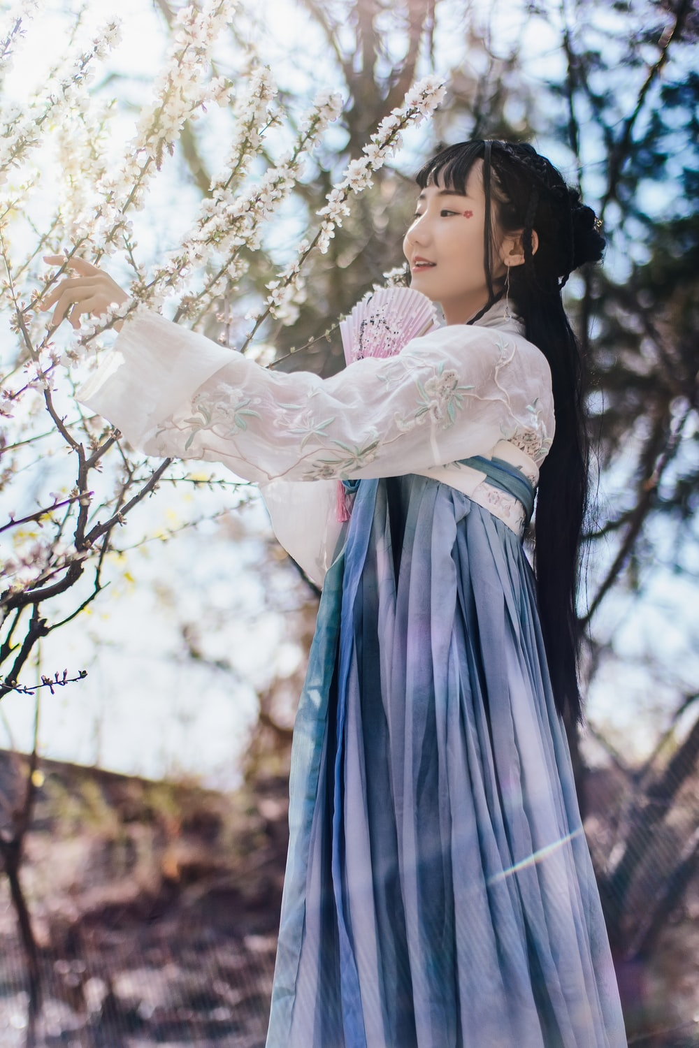 woman in blue and white lace dress near flowering tree