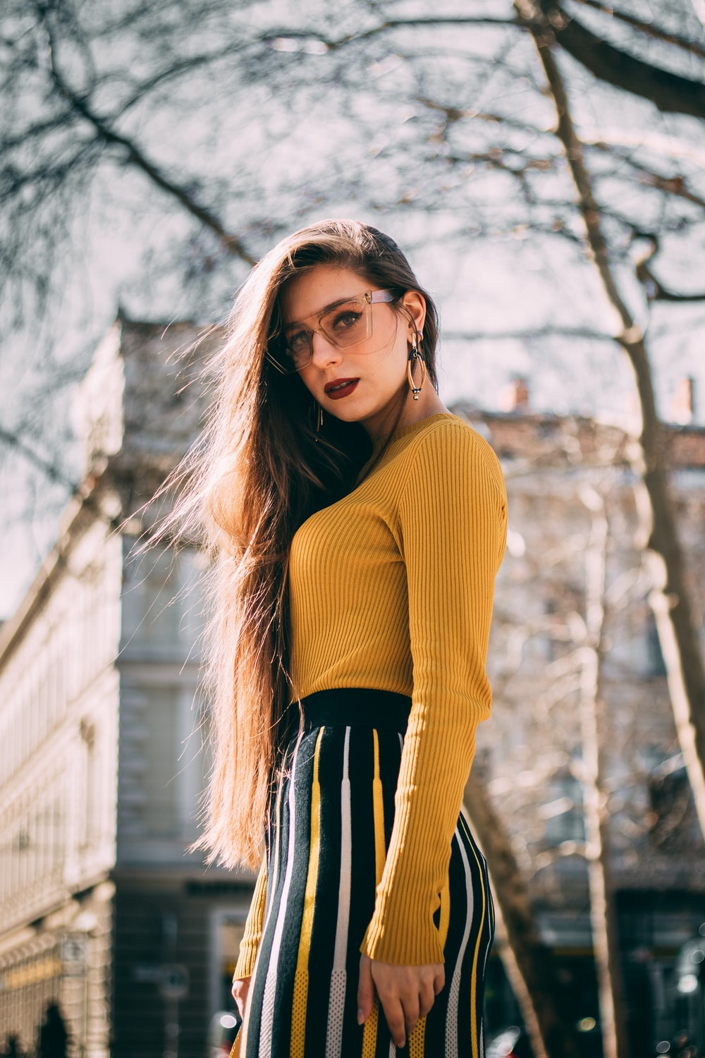 woman in yellow long-sleeve shirt near concrete building during daytime
