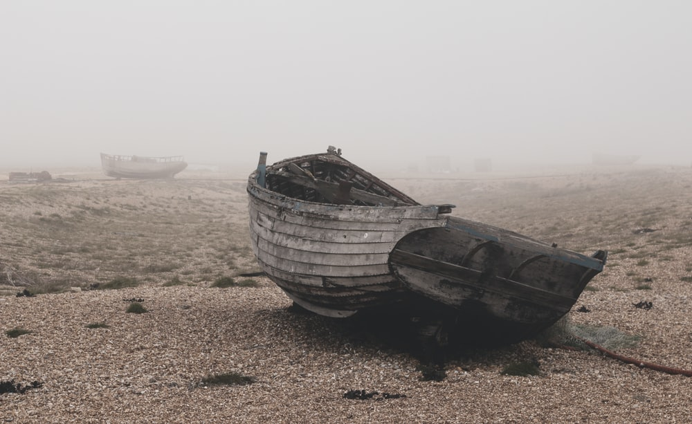 gray boat on brown sand