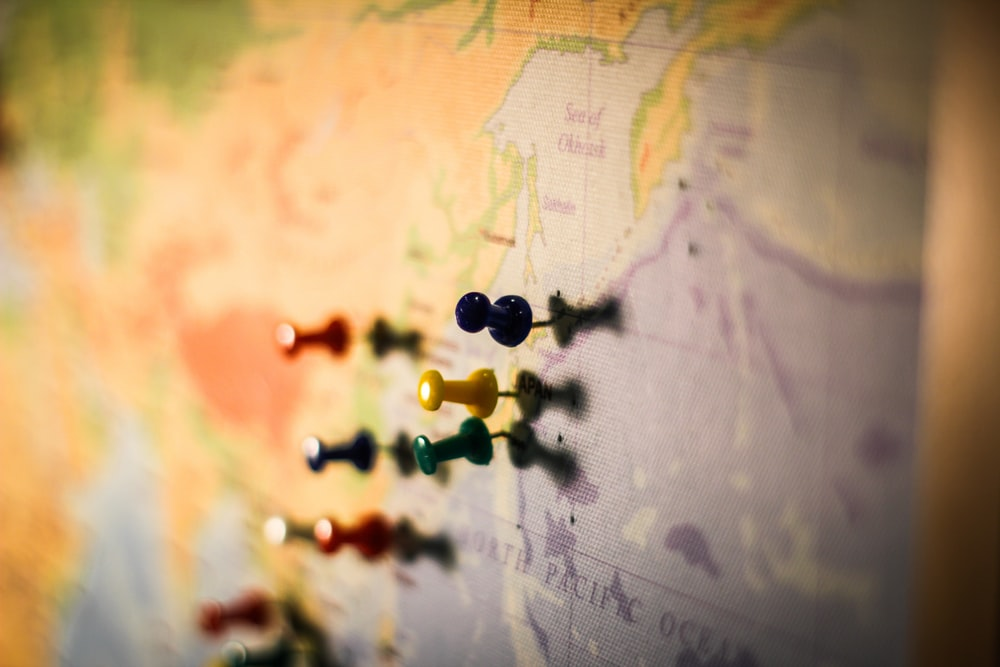 selective focus photography of push pin in map
