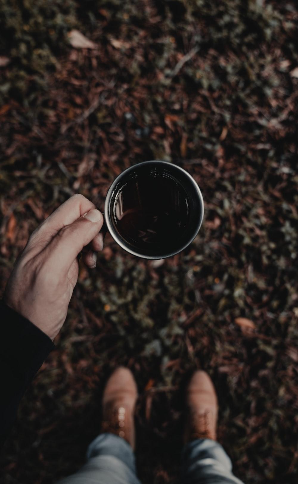 person holding gray coffee mug