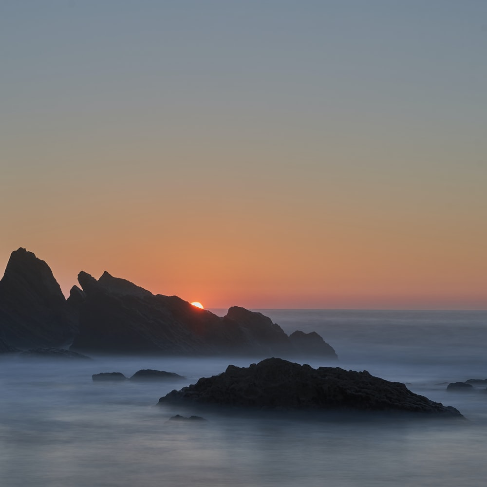 silhouette rock formation during sunset
