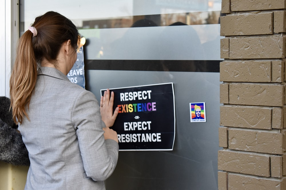 woman posting respect sticker