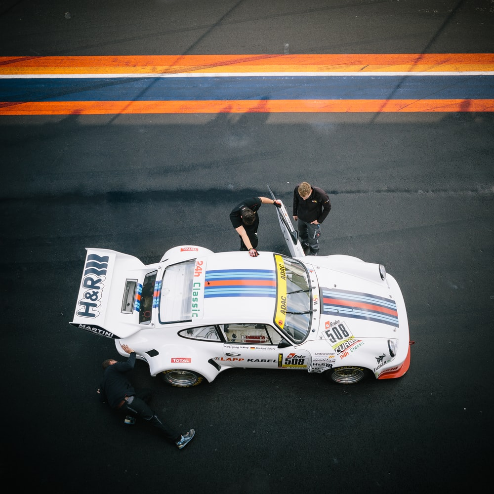 classic white Porsche 911 at pit stop with crew
