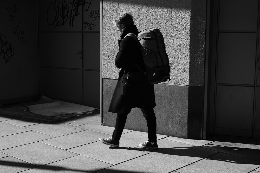 person carrying backpack beside wall