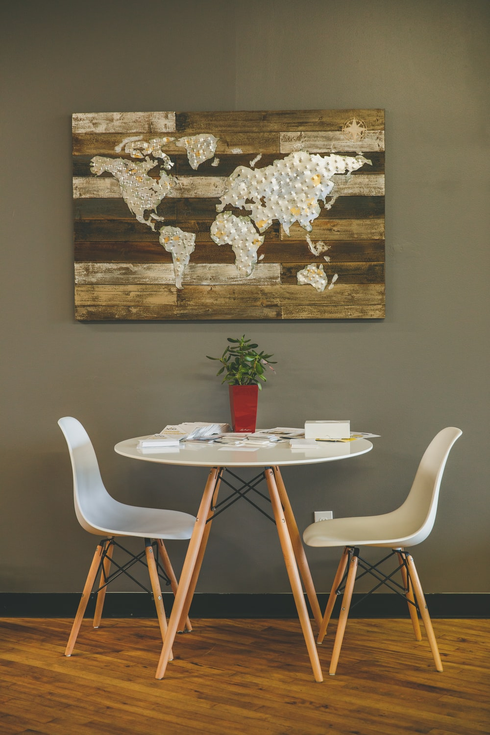 white wooden table with two chairs beside wall