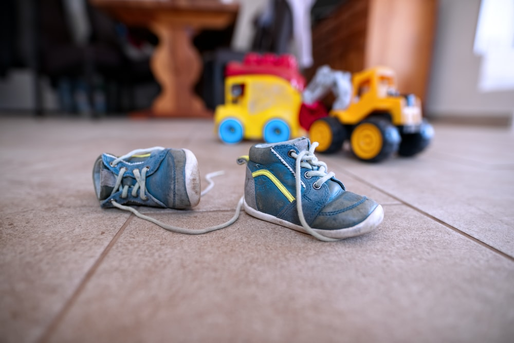 pair of blue sneakers near yellow plastic toys