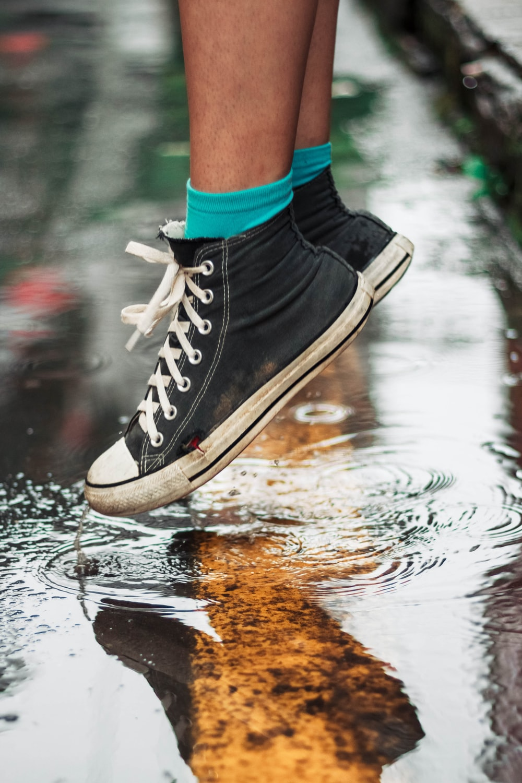 person wearing black high-top sneakers on wet floor