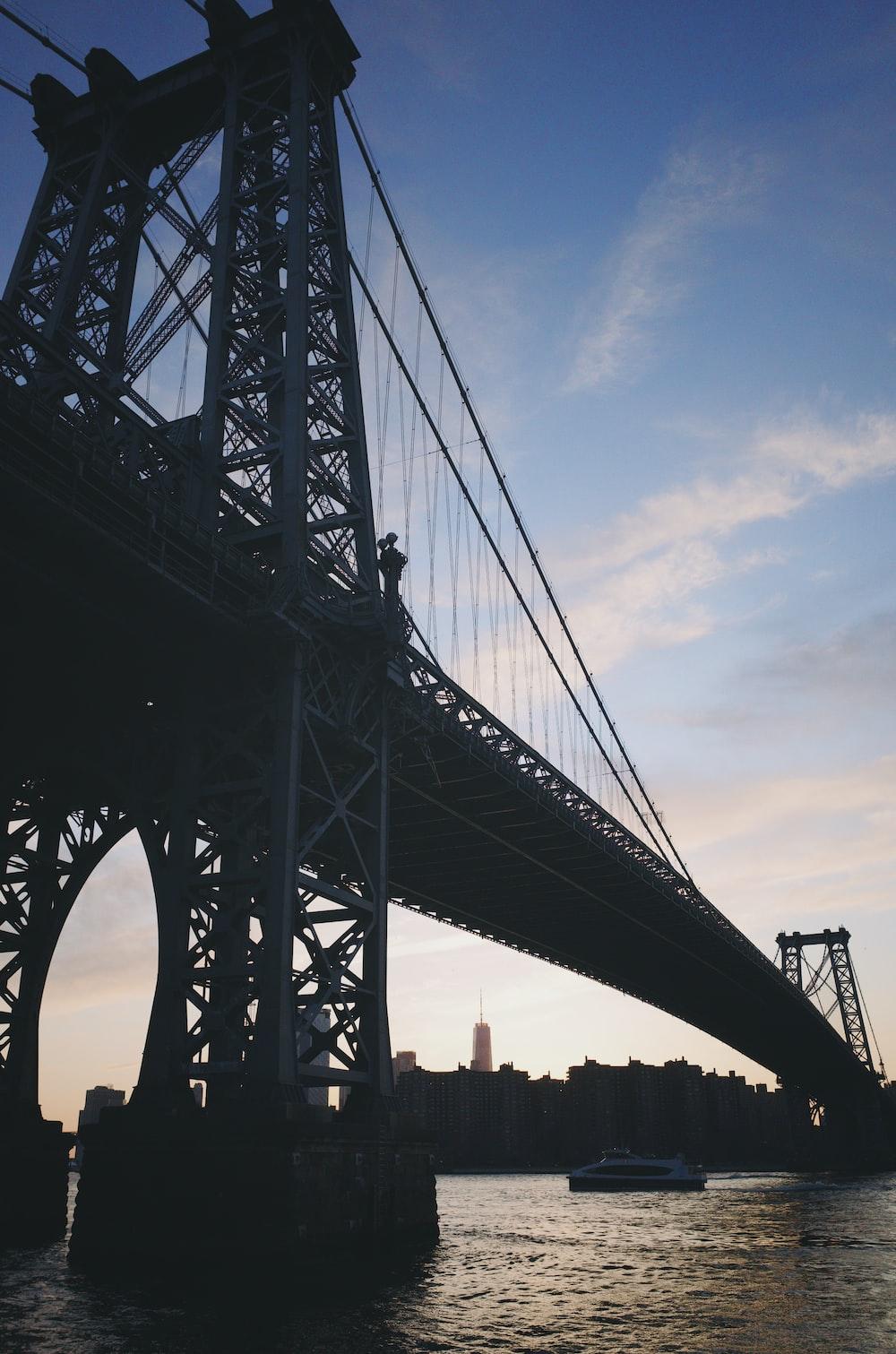 ferry passing under suspension bridge