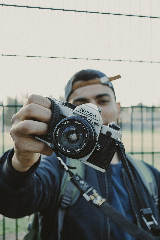 man holding black and white Nikon DSLR camera outdoor during daytime