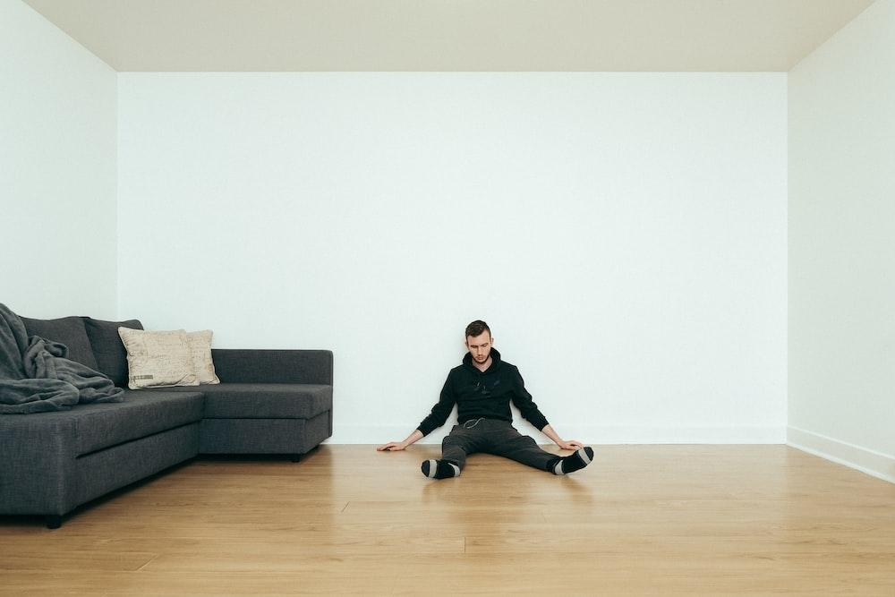 man sitting beside sofa