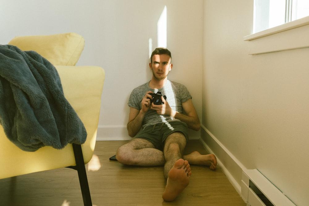 man sitting beside beige sofa chair inside room