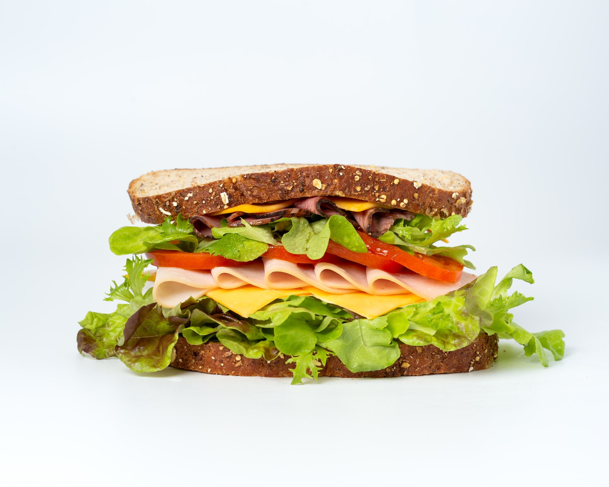 A closeup of a sandwich, showing bread, meat, cheese, and veggies.