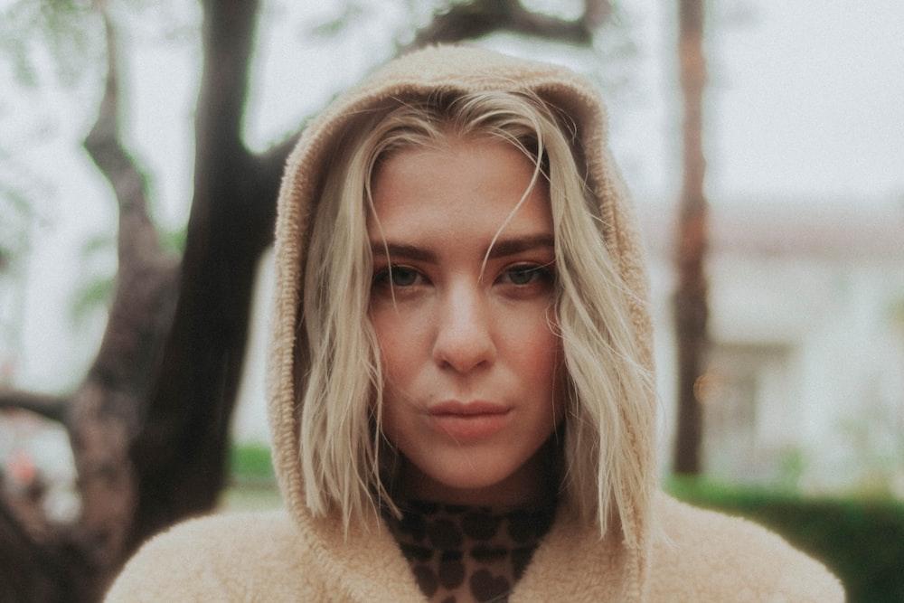woman standing while wearing brown hoodie