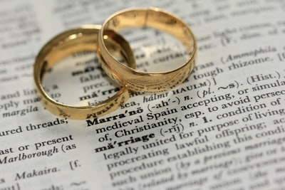 two gold-colored rings on paper marriage zoom background