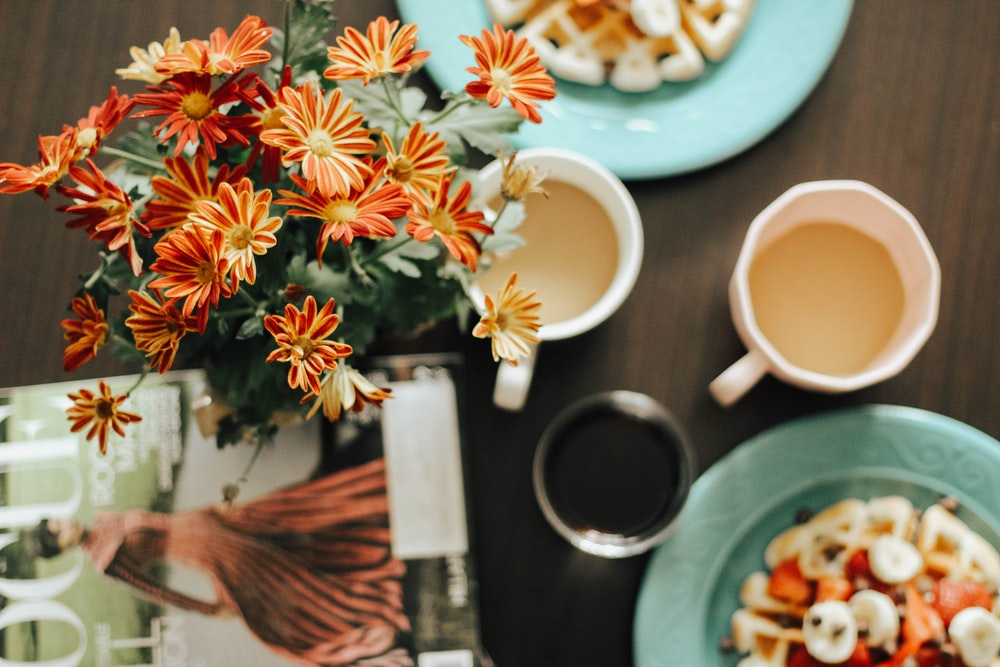 cups, flowers, and plates on brown table